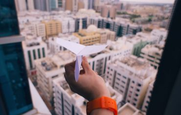 Photo of a paper airplane flying toward a city